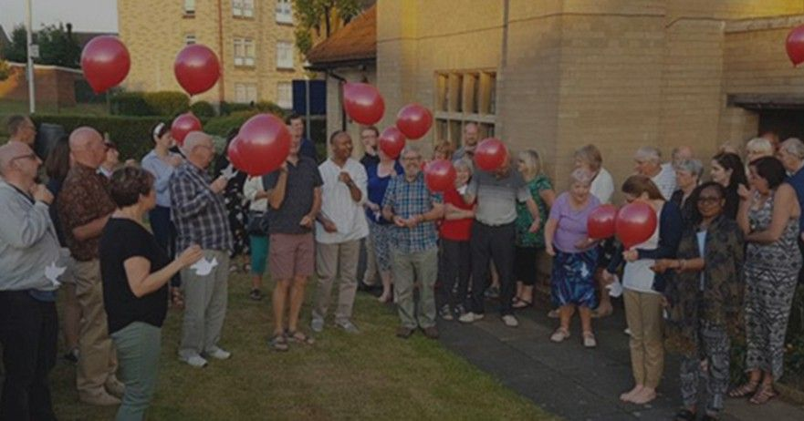 The church congregation outside with balloons.